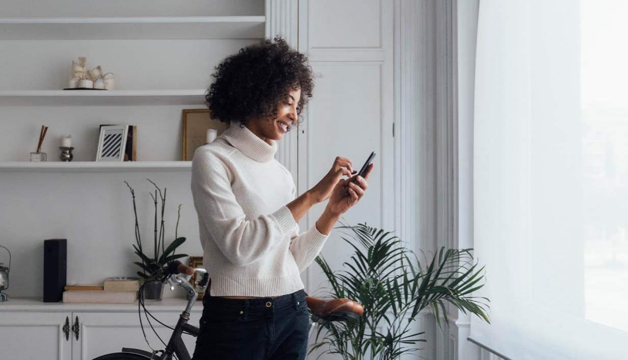 Woman looks at a phone in a living room.