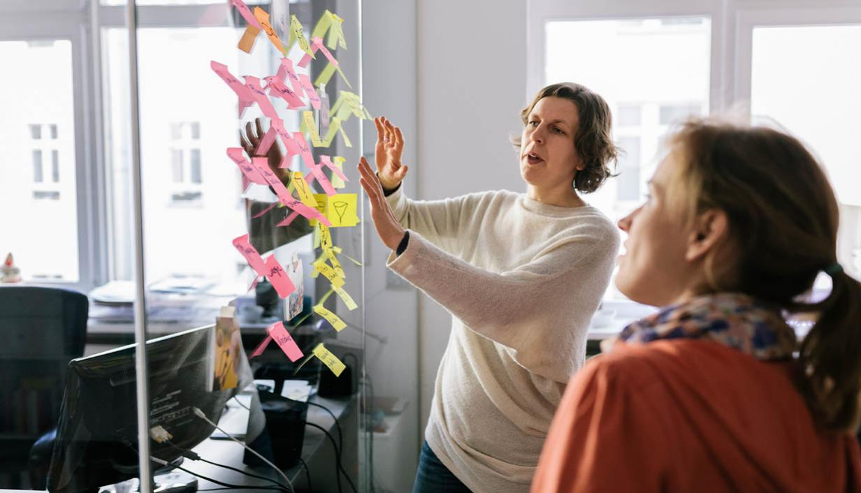 Two women place post-it notes on a glass wall.