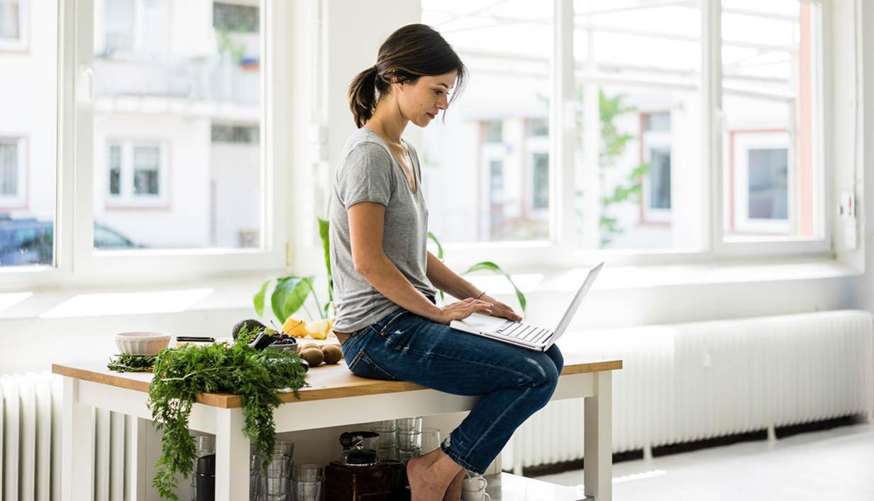Woman types at a laptop in a bright window.