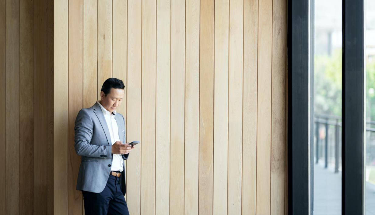 man on phone with wood wall